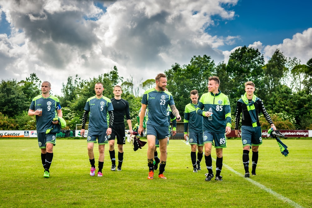 group of men in green soccer jersey shirt on green grass field