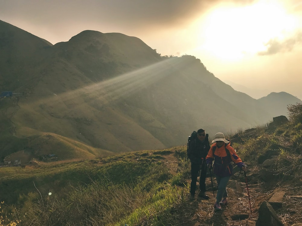 2 people hiking on mountain during daytime