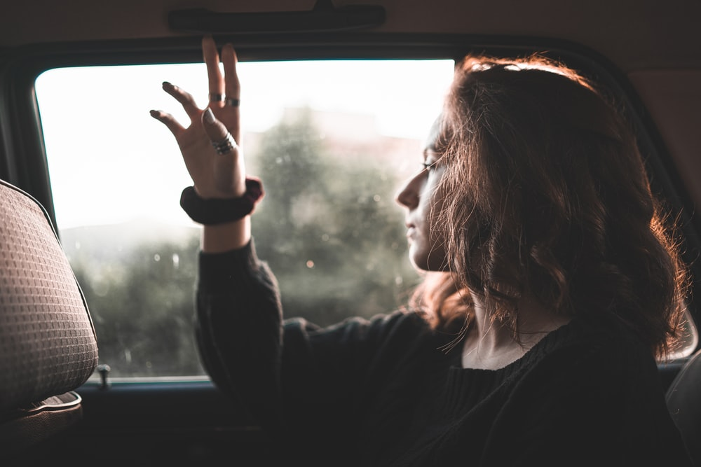 woman in black long sleeve shirt looking at the window