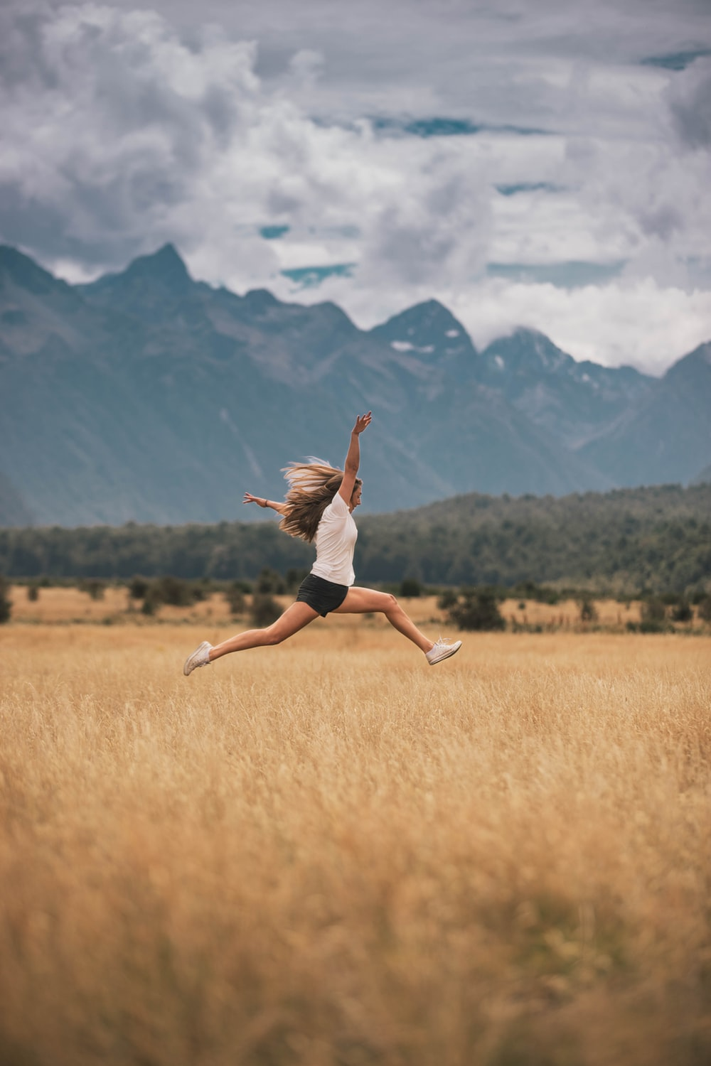 woman in black tank top and white shorts jumping on brown grass field during daytime