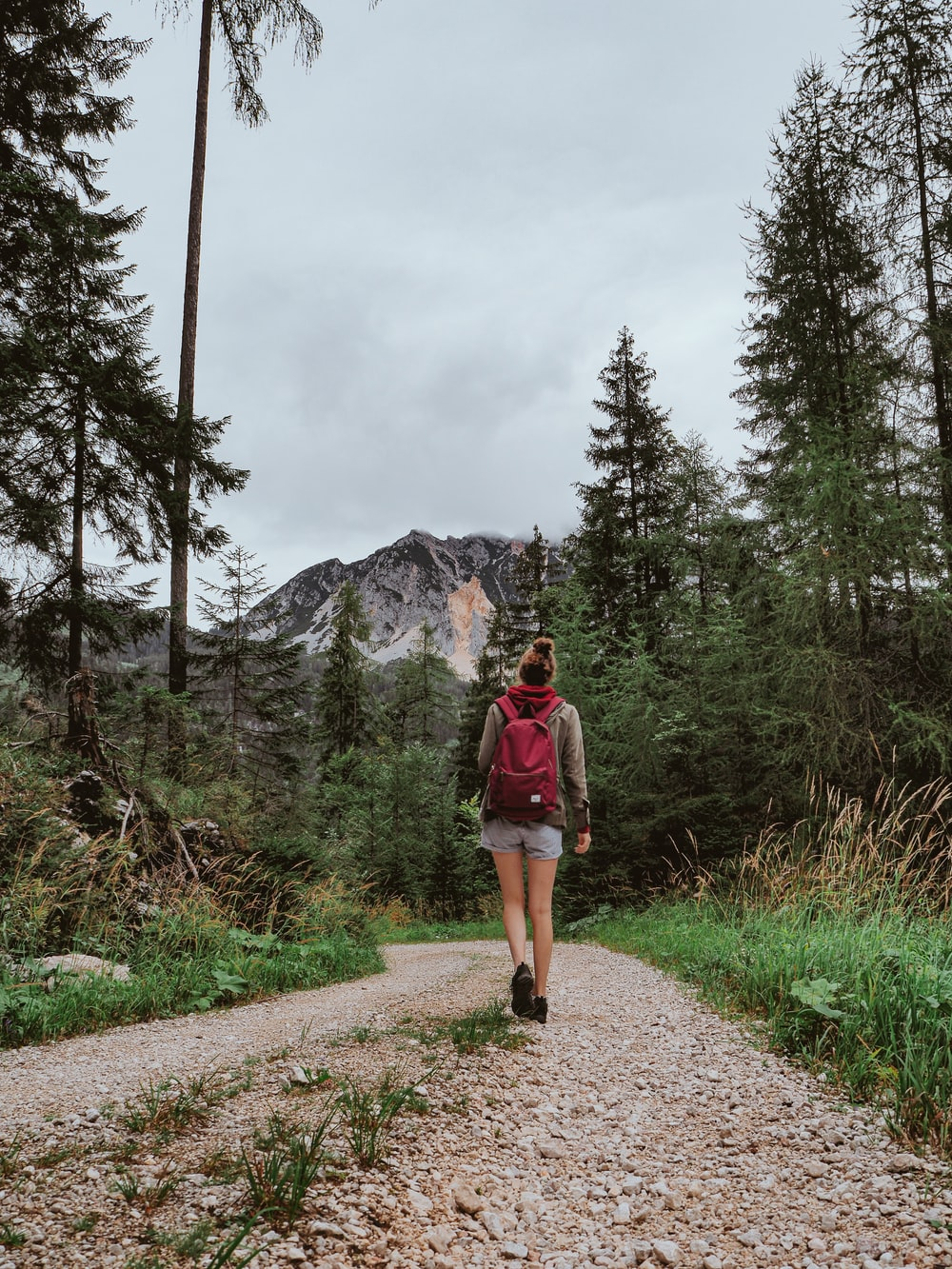 woman in red jacket and brown shorts standing on pathway near green trees and mountain during