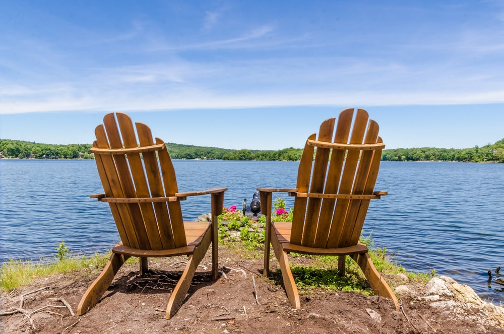 two brown wooden armchairs on beach shore during daytime
