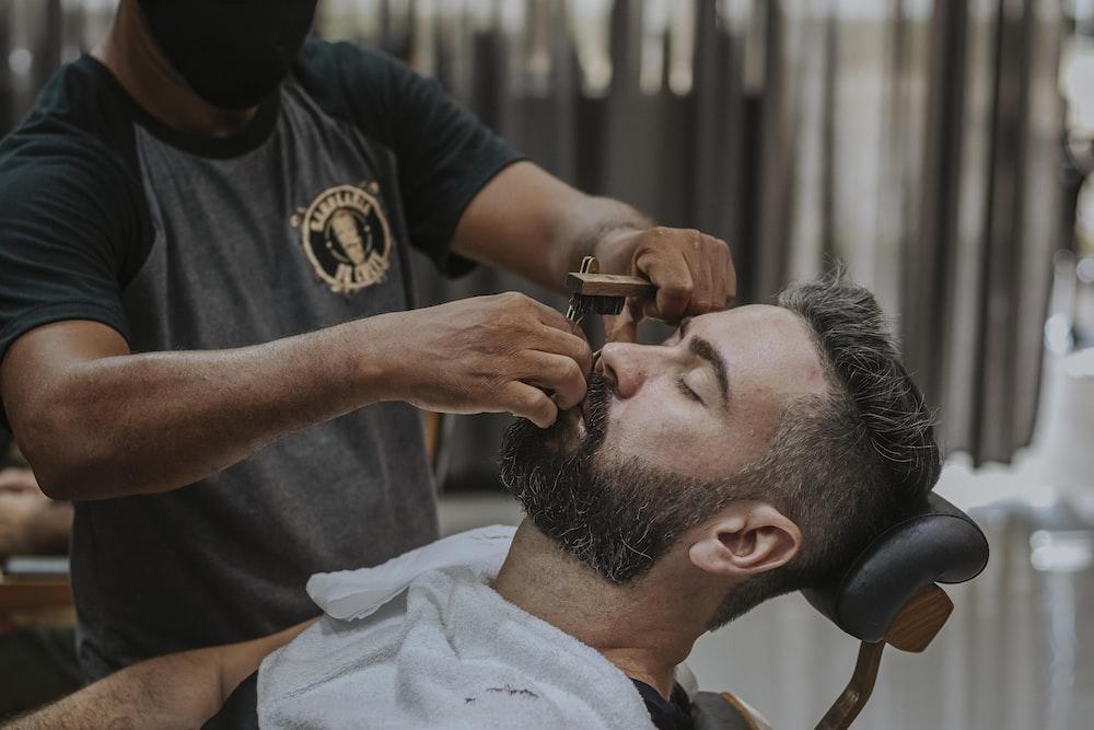 man in black crew neck t-shirt cutting hair of man