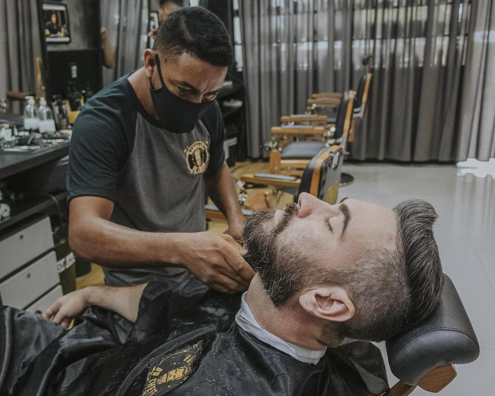 man in black crew neck t-shirt cutting mans hair