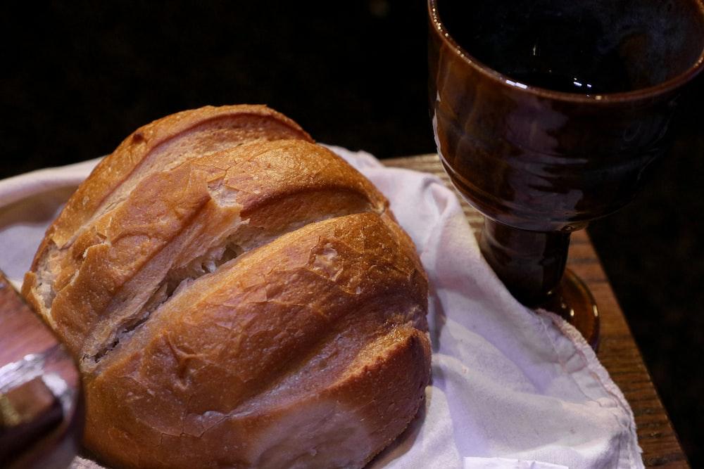 bread on white tissue paper beside black ceramic mug