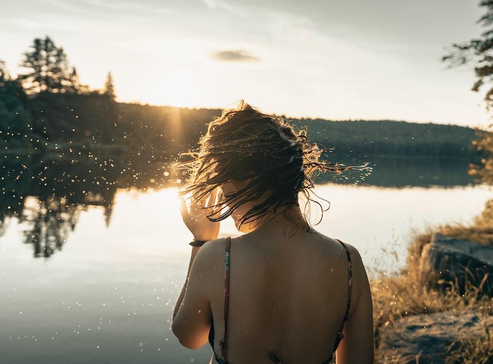 woman in black bikini top standing on water during daytime