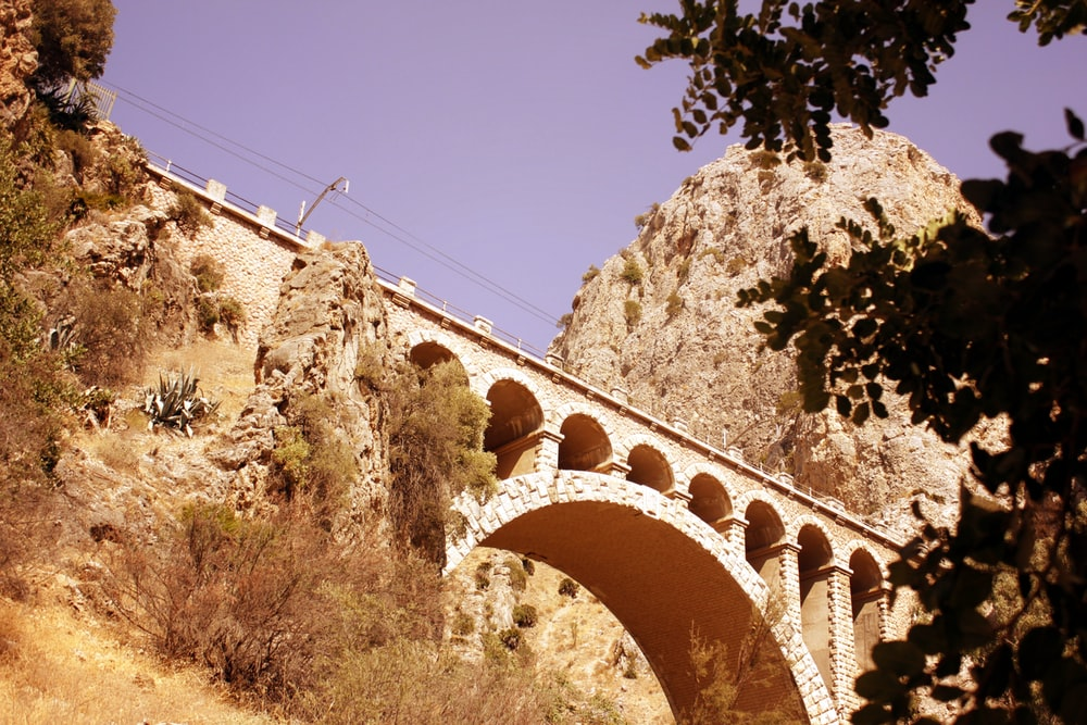 brown concrete bridge under blue sky during daytime