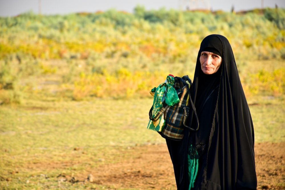 woman in black hijab standing on brown field during daytime