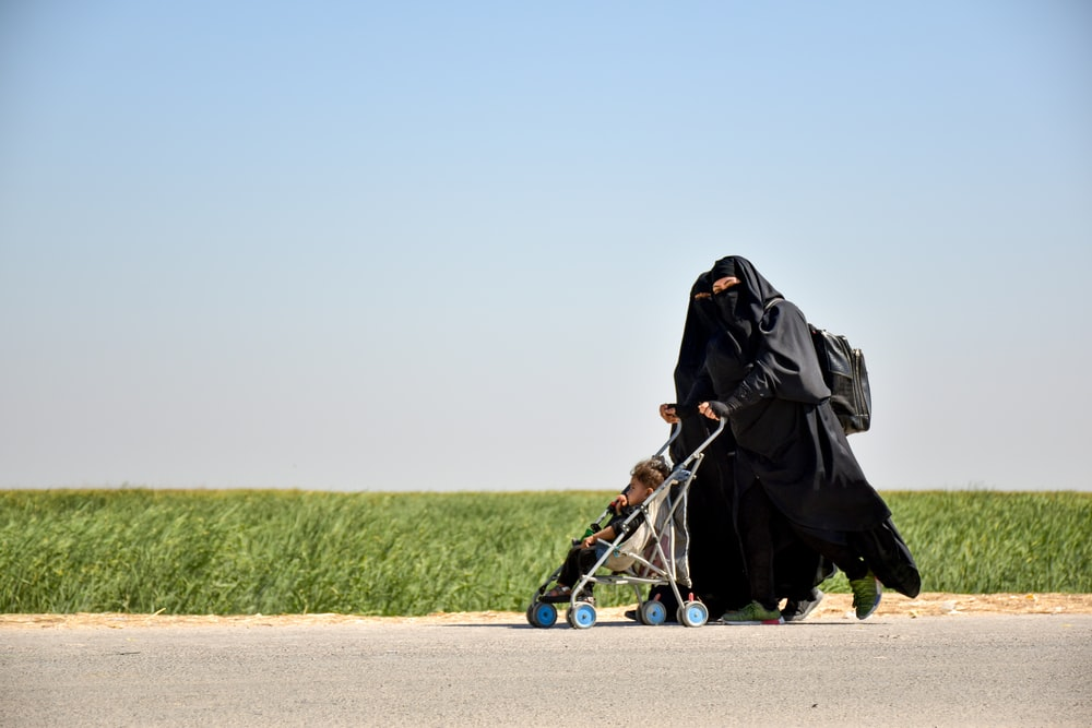person in black robe walking on road during daytime