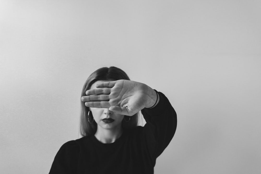 grayscale photo of man in long sleeve shirt covering his face