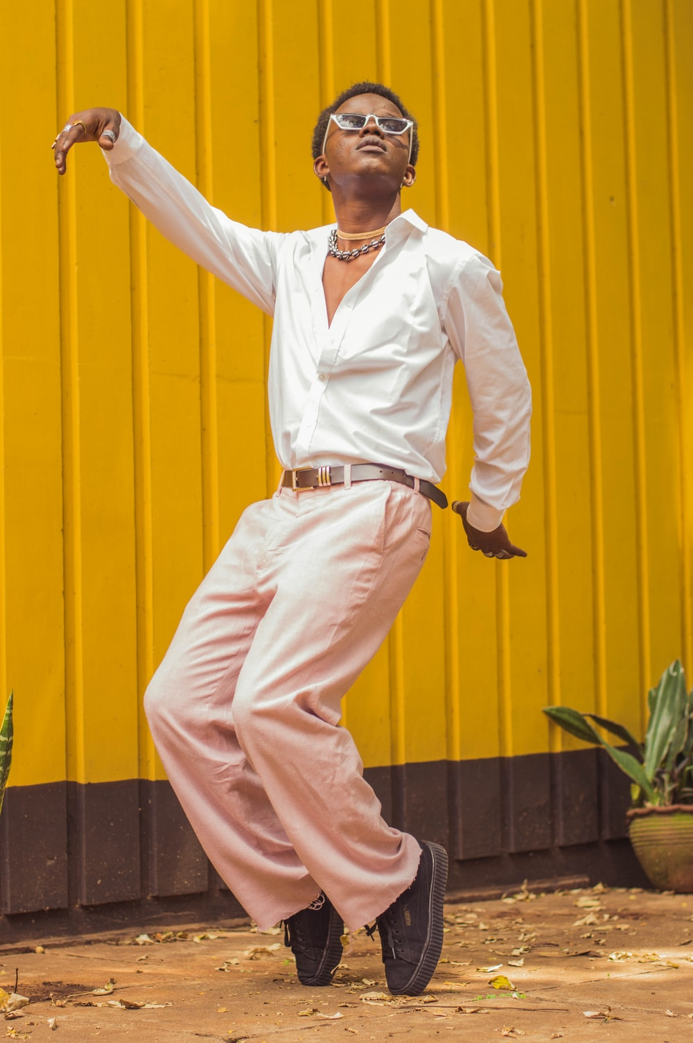 man in white dress shirt and beige pants standing beside yellow wall