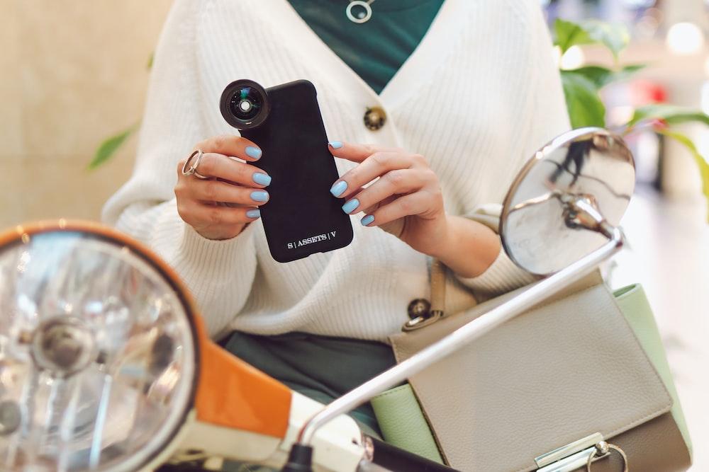 woman in white blazer holding black iphone 5