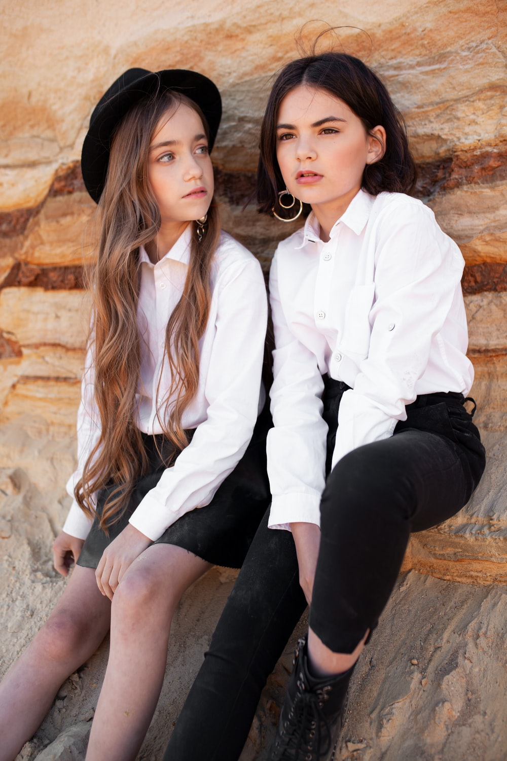 2 women in white dress shirt and black pants sitting on brown rock