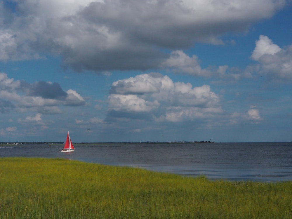 white and red sailboat on sea under white clouds and blue sky during daytime