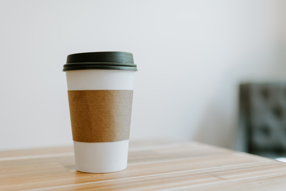 white and brown paper cup