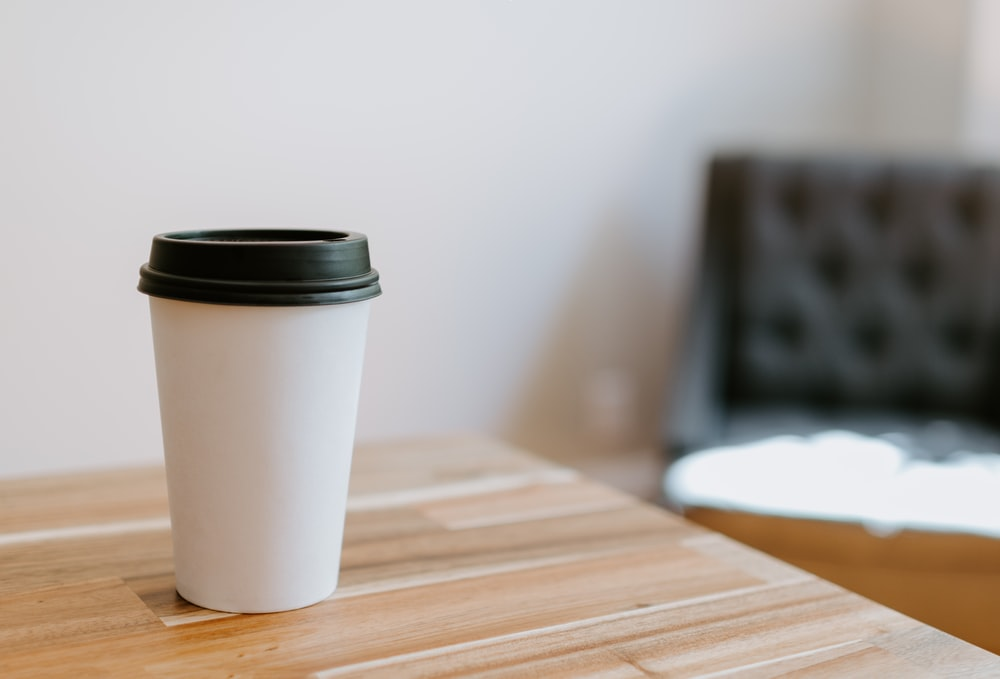 white disposable cup on brown wooden table