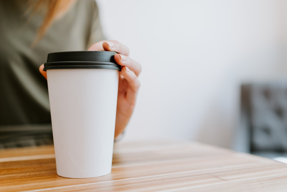 person holding white disposable cup
