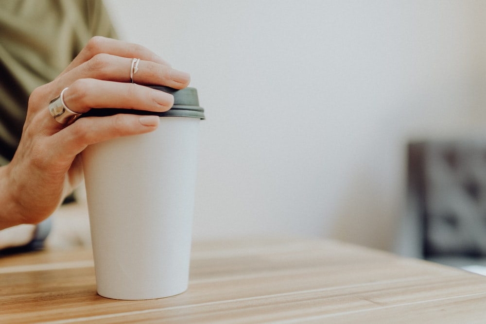 person holding white paper cup