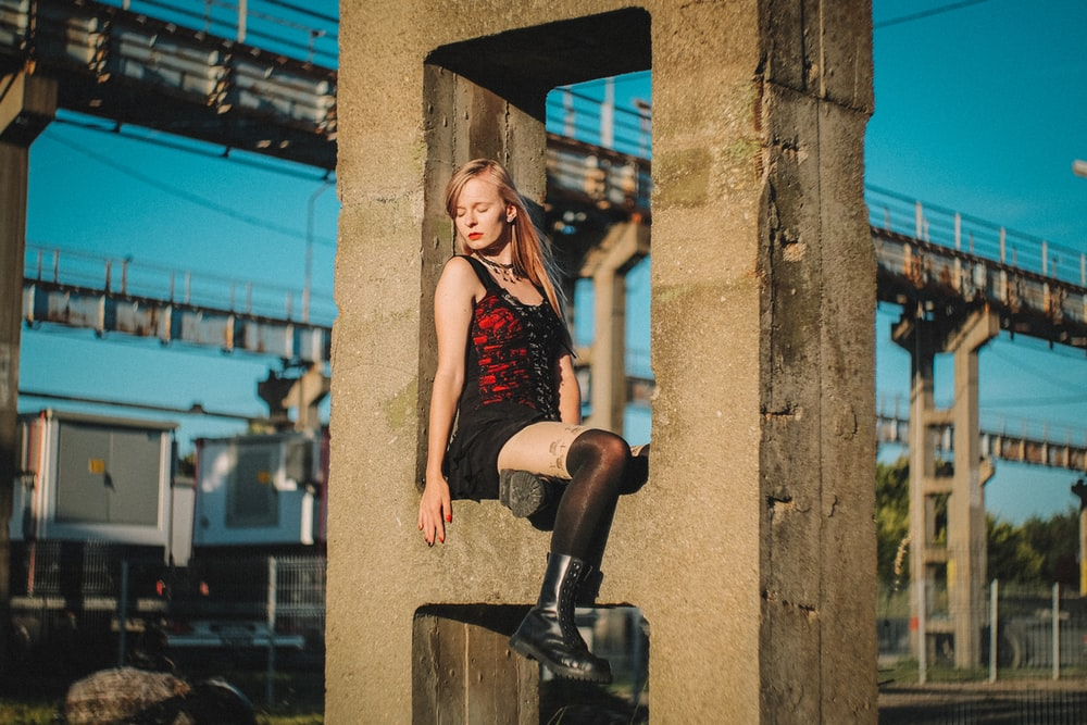 woman in red tank top and black shorts sitting on black metal post during daytime