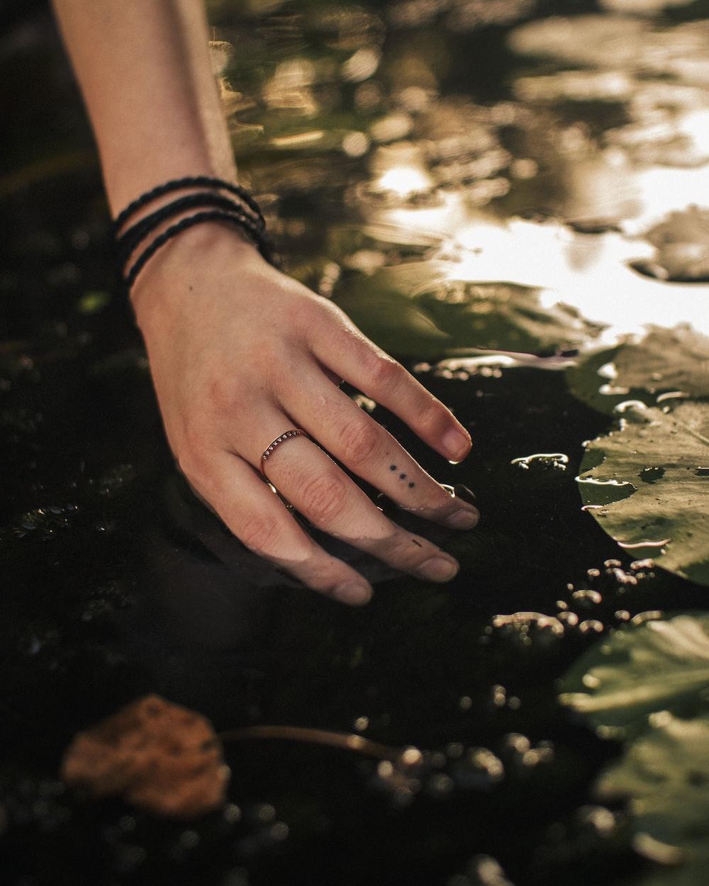 person wearing silver link bracelet watch holding black stone