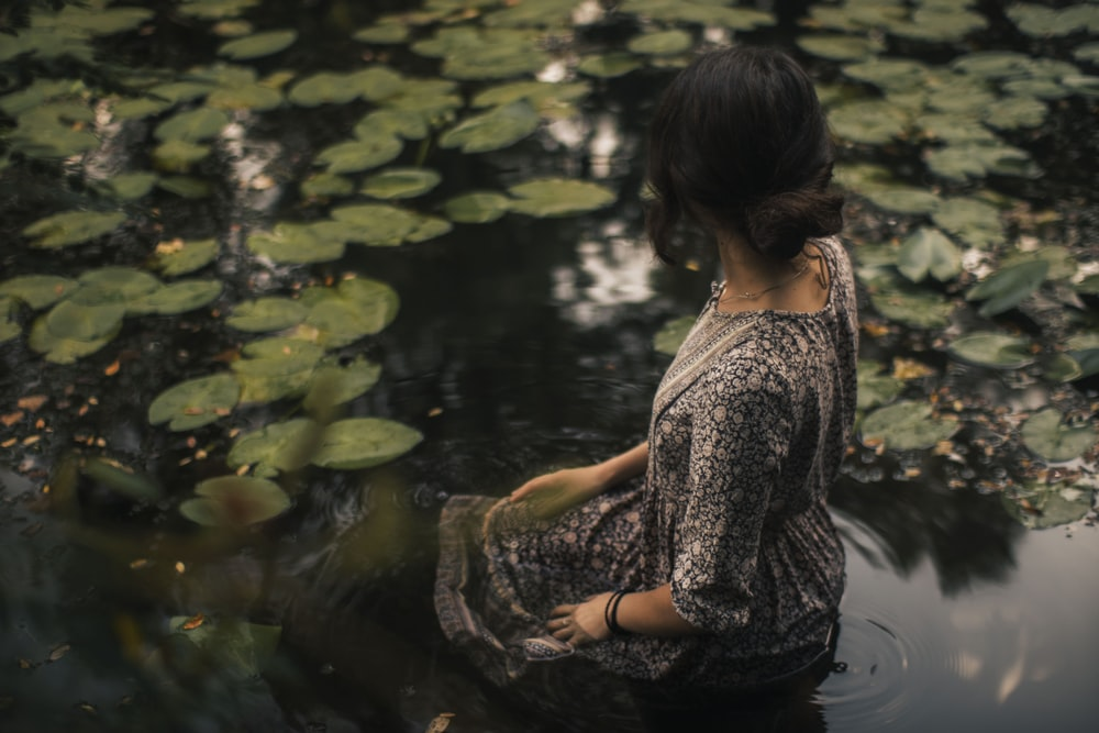 woman in black and white floral dress sitting on water
