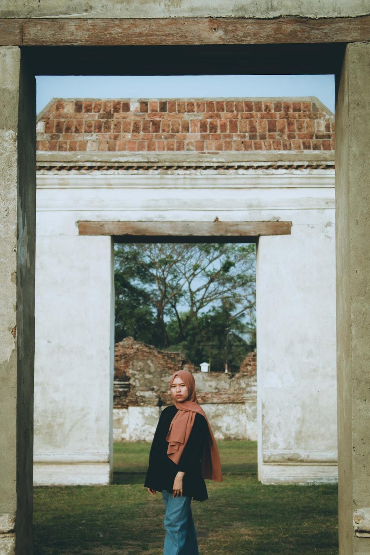 man in black and orange jacket standing near brown brick wall
