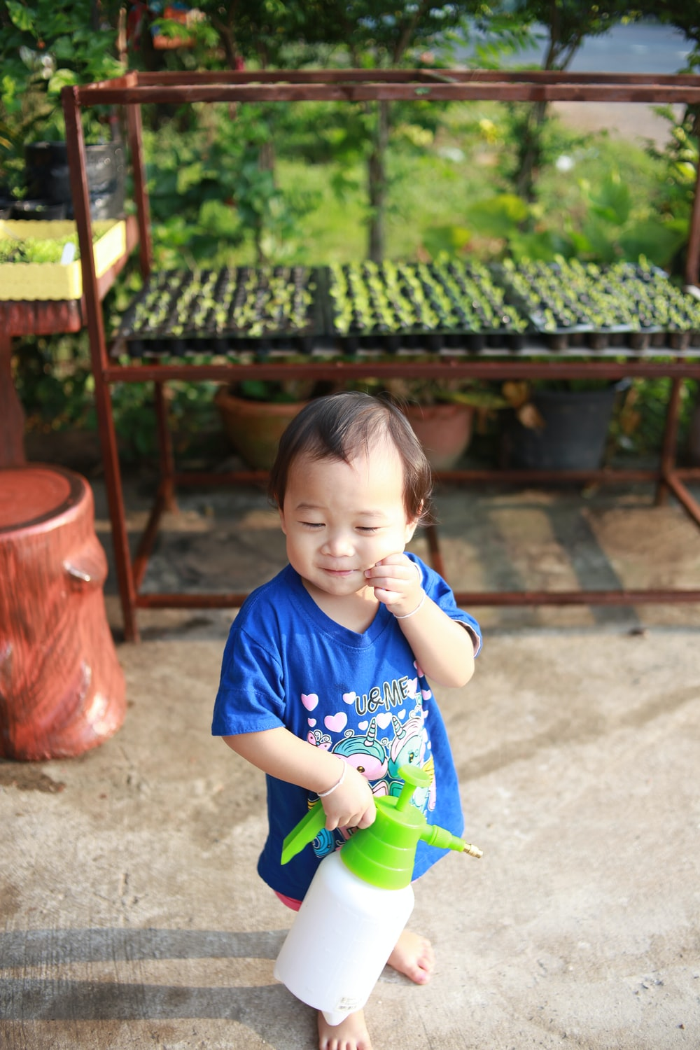 girl in blue crew neck t-shirt holding green plastic toy