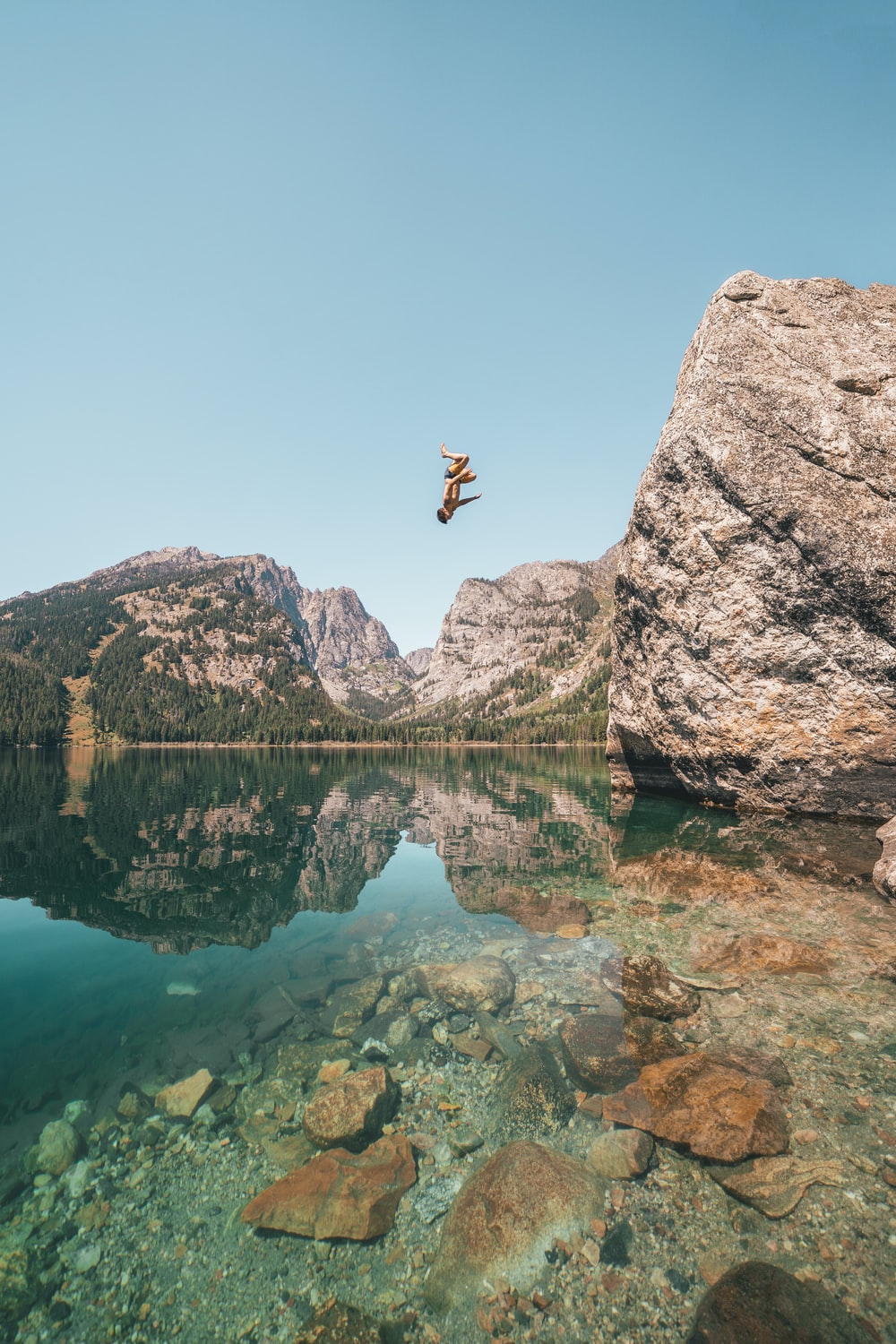 person jumping from rock formation to lake during daytime