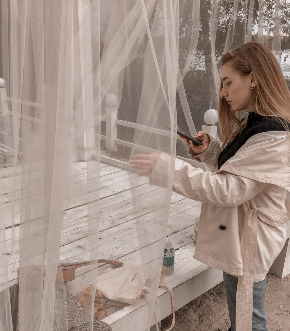 woman in white coat standing beside glass window