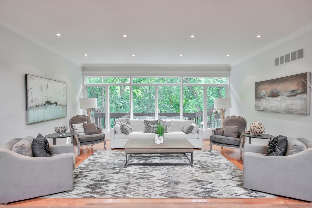 living room with white and brown area rug and brown leather armchair