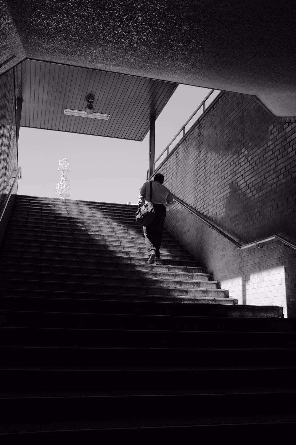 man in black jacket and pants walking on stairs