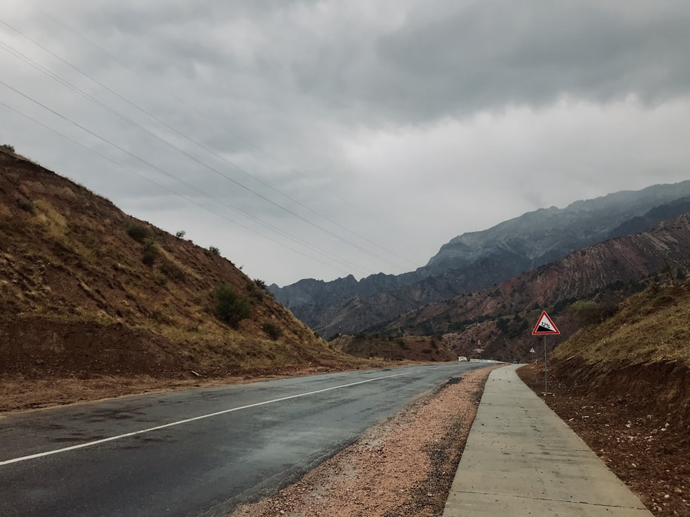 gray concrete road near mountain under gray sky