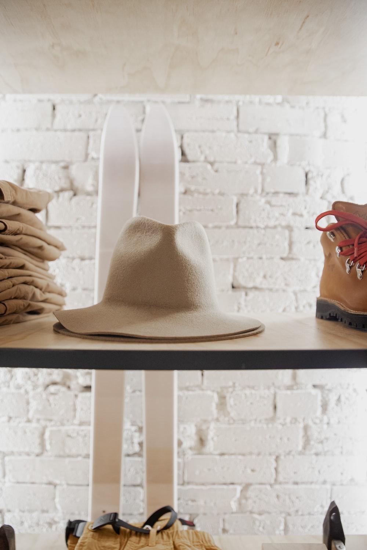 brown cowboy hat on black wooden shelf