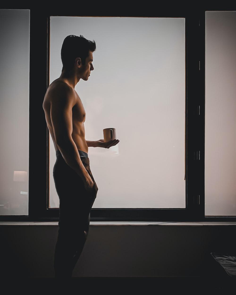 topless man in black pants holding black ceramic mug