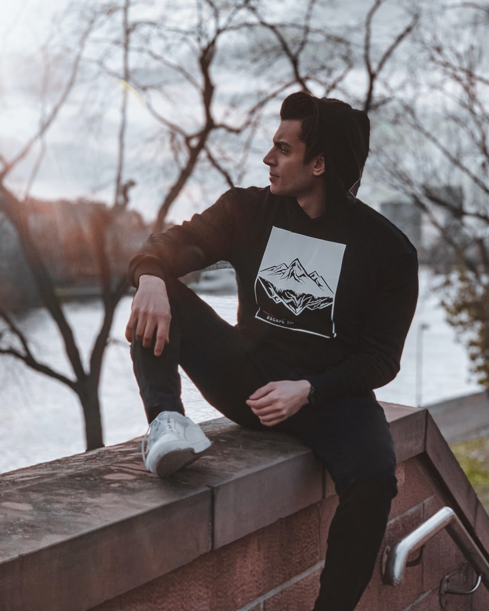 man in black long sleeve shirt sitting on brown wooden bench during daytime