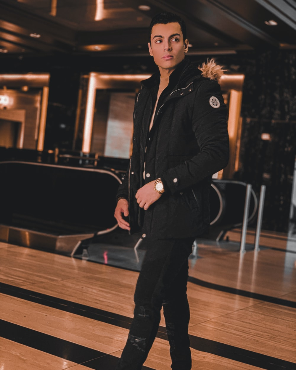 woman in black coat and black pants standing on brown wooden floor