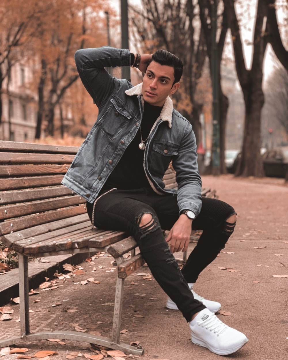 man in black leather jacket sitting on brown wooden bench during daytime