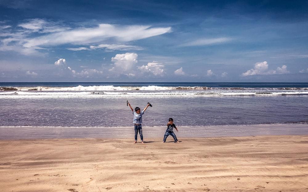 2 women standing on beach during daytime