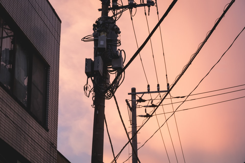 black electric post near brown concrete building during daytime