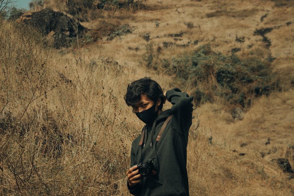 man in black hoodie standing on brown grass field during daytime