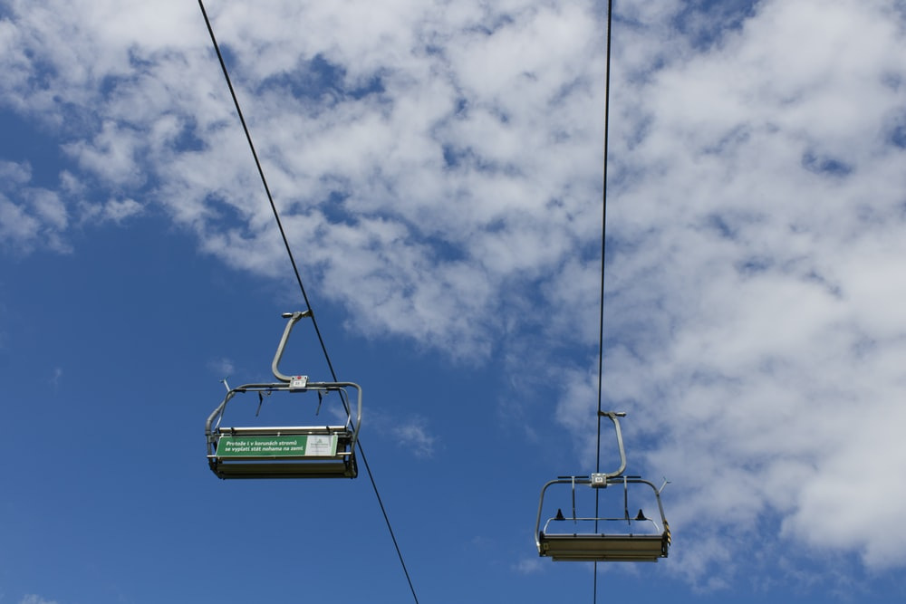 green and white cable car under cloudy sky