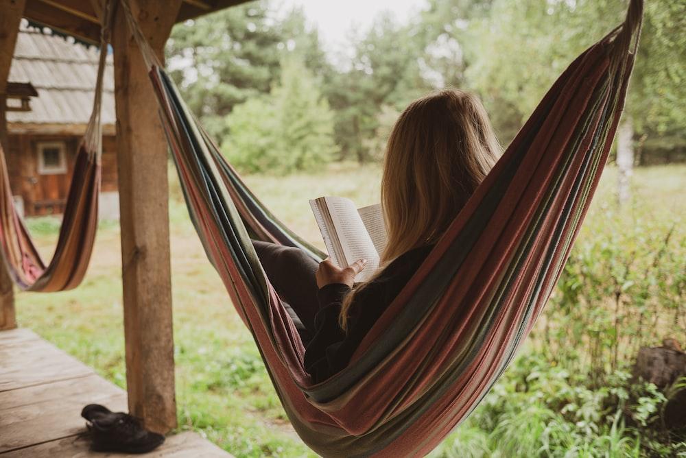 woman reading book on hammock