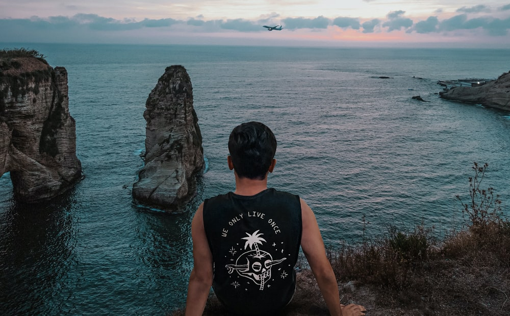 man in black tank top standing on rock near sea during daytime