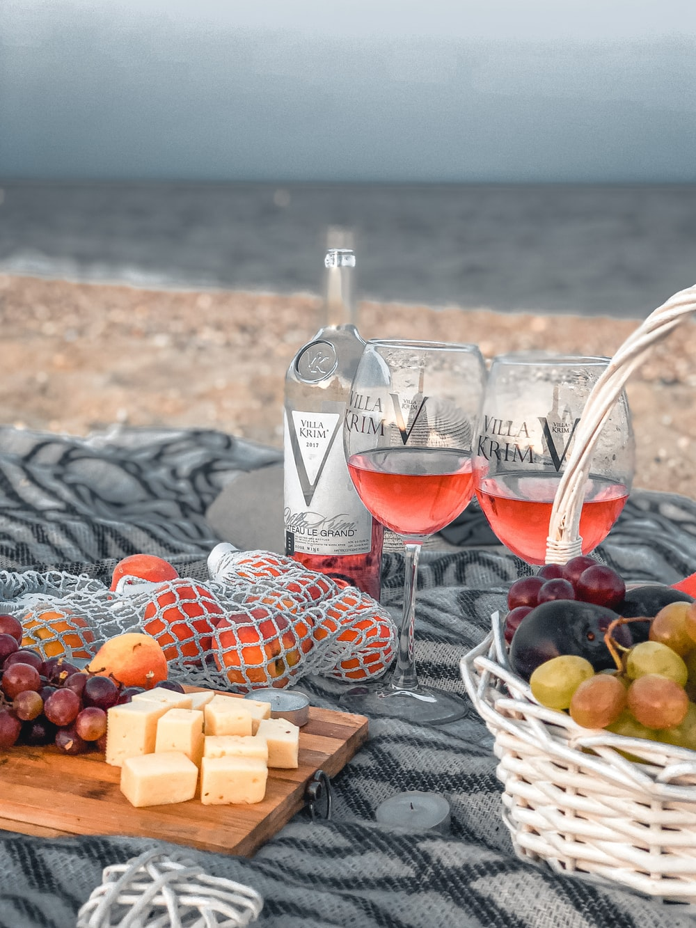 clear wine glass with red wine beside brown woven basket on black and white textile