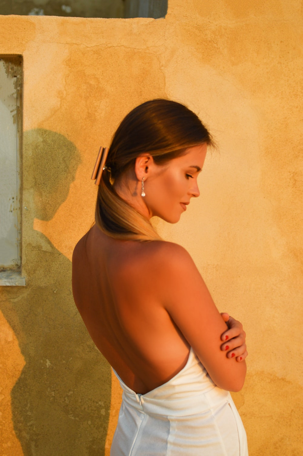 woman in white panty leaning on wall