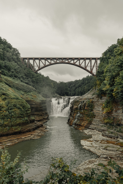 water falls under gray bridge