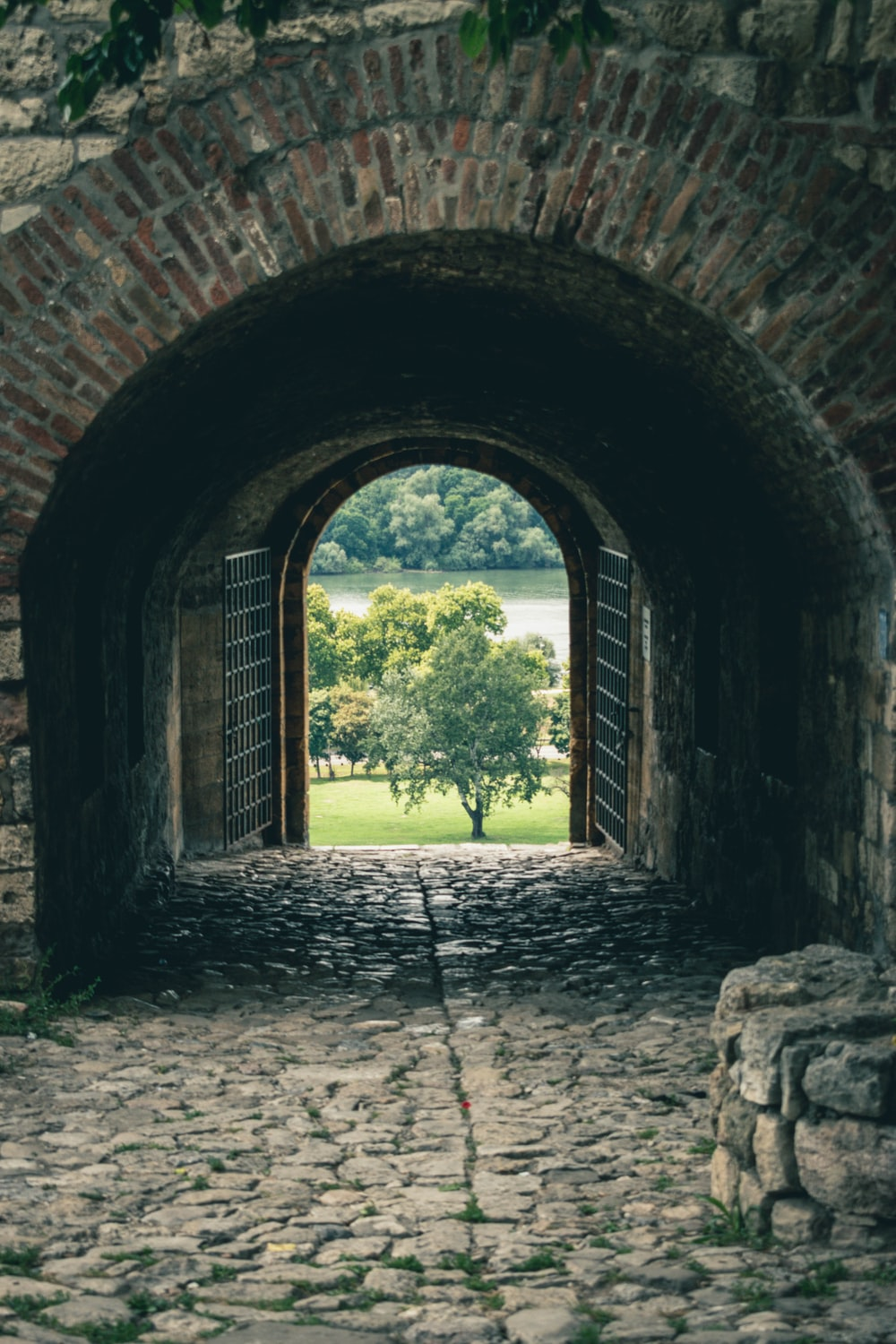 brown brick tunnel with green trees