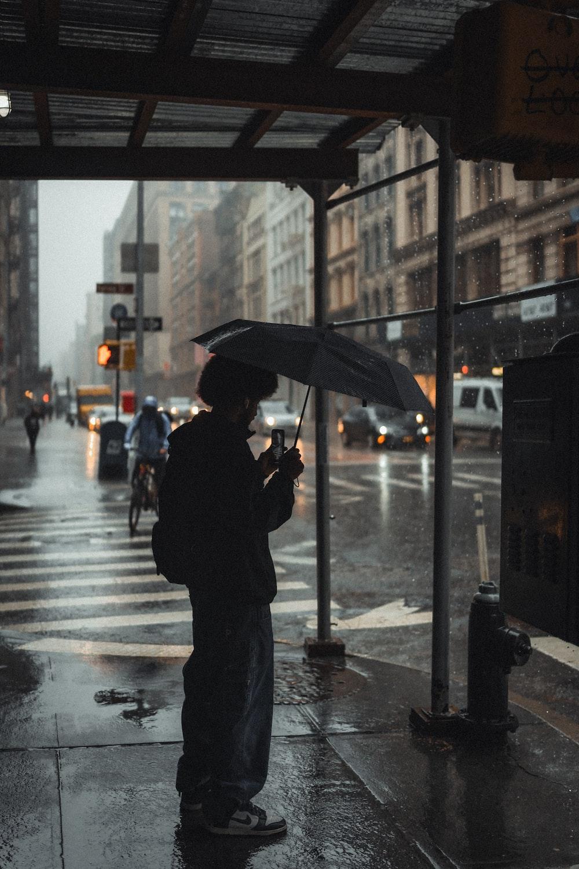 man in black jacket holding umbrella standing on sidewalk during daytime