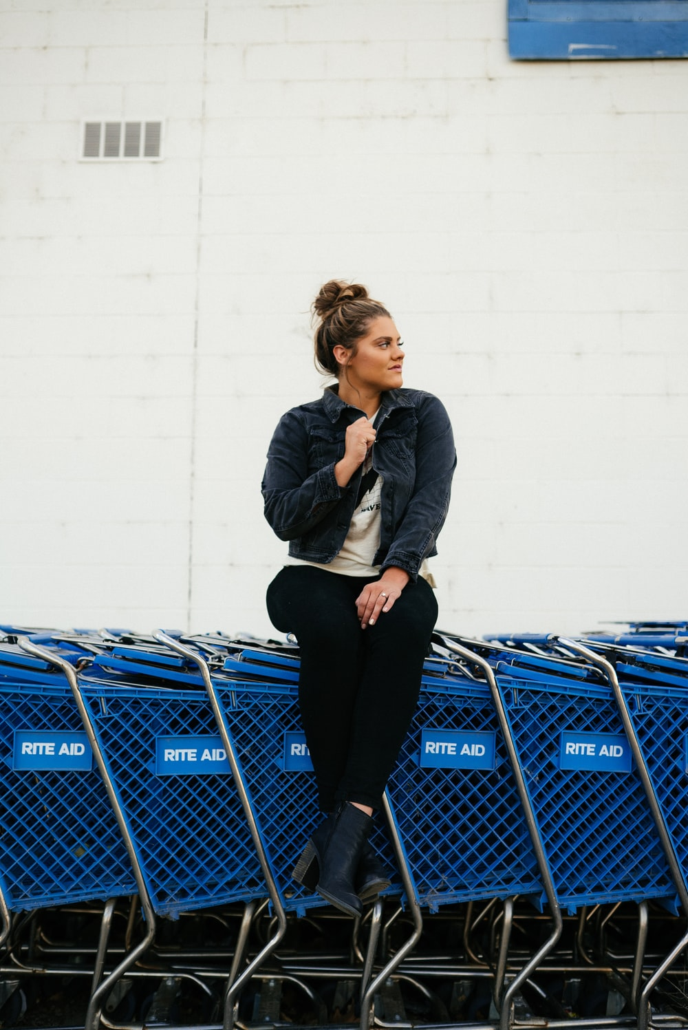 woman in gray jacket and black pants standing beside blue shopping cart