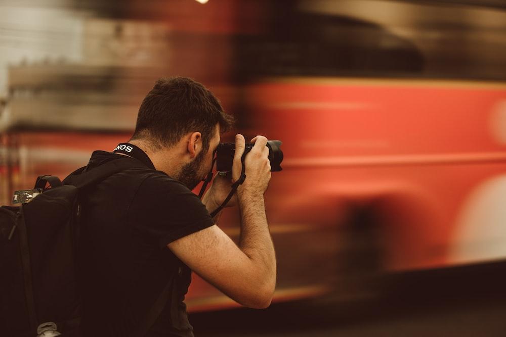 man in black t-shirt holding black camera